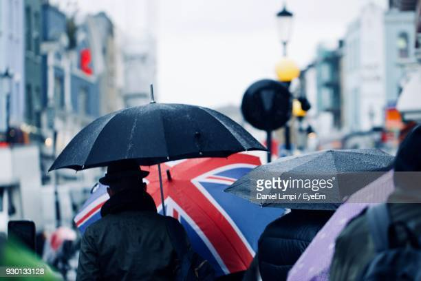 people with umbrella walking in city during rainy season - britain stock pictures, royalty-free photos & images