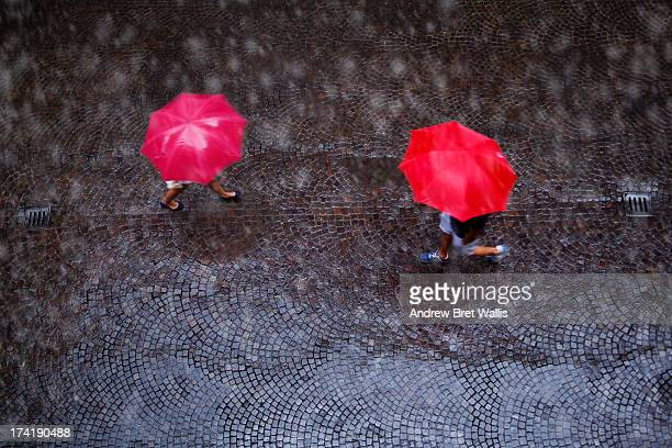 People with umbrellas cross paths in the rain