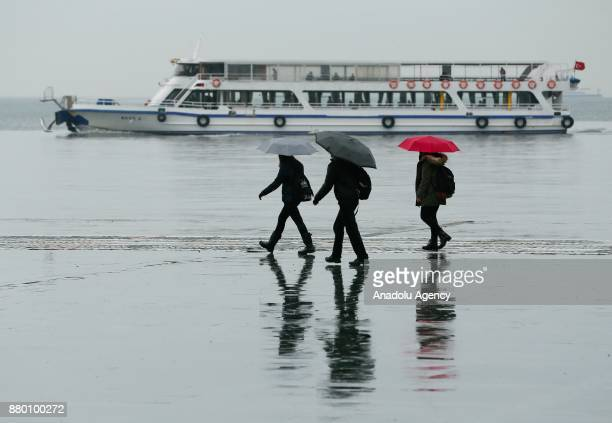People with umbrellas walk over a wet floor after heavy rainfalls hit Izmir Turkey on November 27 2017 People try to prevent getting caught in...