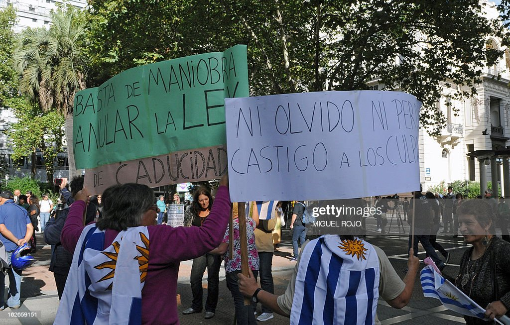 People with Uruguayan national flags hold signs reading 'Stop the maneuver. Annul the Law of Expiry' and 'Neither obscurity nor pardon. Punishment to the guilty', during a protest in front of the Supreme Court of Justice on February 25, 2013 in Montevideo, after the Court's decision to declare unconstitutional a law of 2011 which considered imprescriptible the crimes committed during the last military dictatorship (1973-1984) in Uruguay. AFP PHOTO/Miguel ROJO