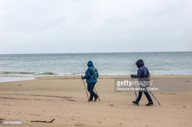 People With Walking Poles At Beach Against Sky