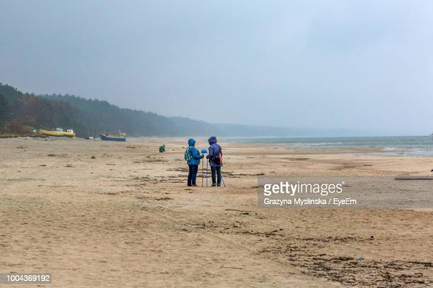 People With Walking Poles Standing At Sandy Beach Against Sky