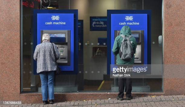 People withdraw cash from Halifax Bank on October 28, 2020 in Stoke, England. HSBC Chief Executive Noel Quinn said the bank will review pricing...