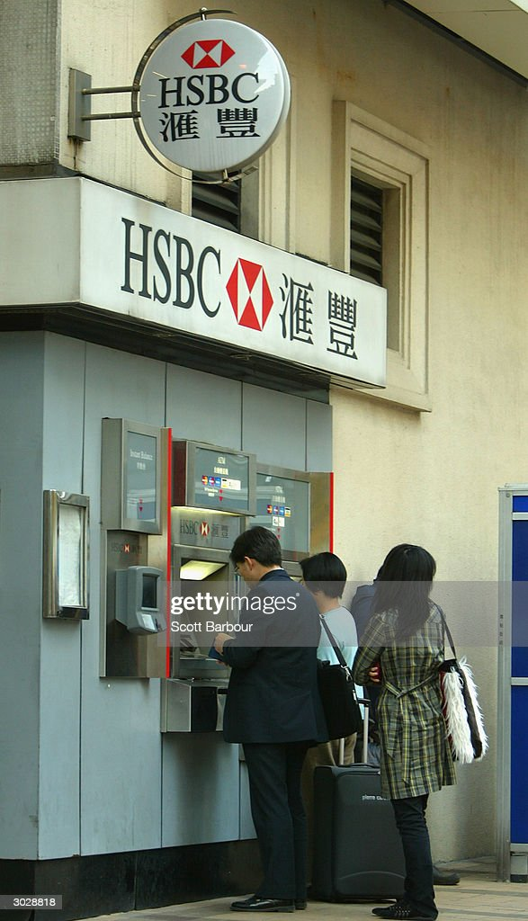 People withdraw money from a cash machine of the banking giant HSBC on December 11, 2003 in Hong Kong. The London-based bank, which operates in 79 countries, gave an upbeat tone for the global economy March 1, 2004 including its key Hong Kong market by reporting a record annual pre-tax profit of ?7.7bn ($14.4).