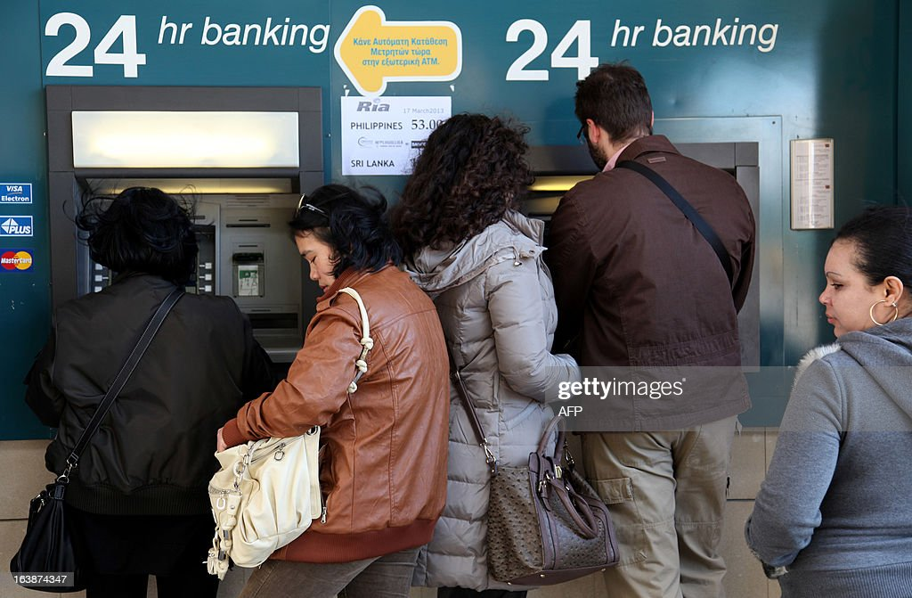 People withdraw money from a cash-point machine in the Cypriot capital Nicosia on March 17, 2013. The Cyprus government postponed a planned emergency session of parliament on Sunday to debate a controversial EU bailout, state media said, as the scale of opposition to its terms became clear.