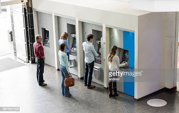 people withdrawing cash at an atm - fileira - fotografias e filmes do acervo