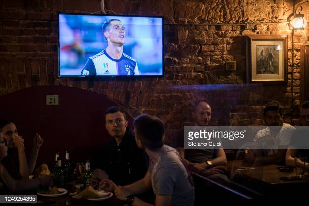 People without protective mask drink a beer and watch on the screen Cristiano Ronaldo play in the Coppa Italia Semi-Final Second Leg match between...