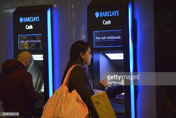 People withrdawing cash from a cash machine at a branch of Barclays Bank in Manchester Greater Manchester England United Kingdom on Tuesday 1st March...