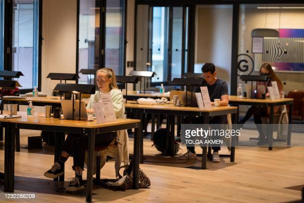 People work at a shared workspace at the WeWork, coworking and office space in the City of London, on April 13 as the company enhances health and...