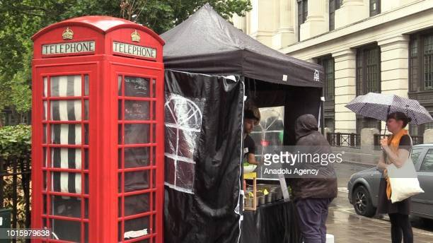 People work at an iconic Red English Telephone booth used as a falafel and salad bar at Hollborn district of London United Kingdom on August 13 2018