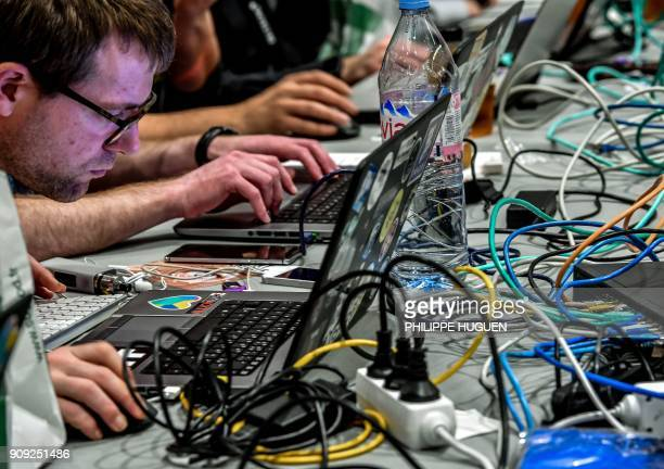 People work at computers during the 10th International Cybersecurity Forum in Lille on January 23 2018 / AFP PHOTO / Philippe Huguen