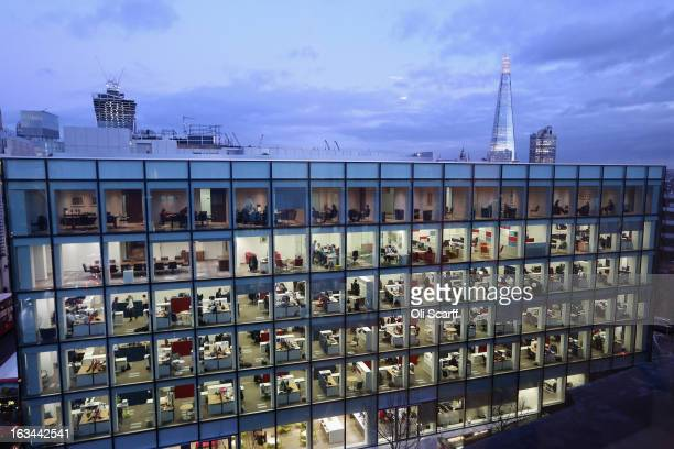 People work at dusk on various floors of the modern office development at 20 Cannon Street near St Paul's Cathedral on February 06, 2013 in London,...
