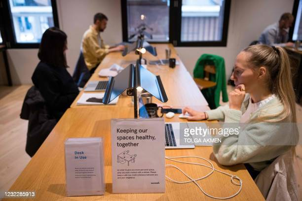 People work at shared workspaces at the WeWork, coworking and office space in the City of London, on April 13 as the company enhances health and...