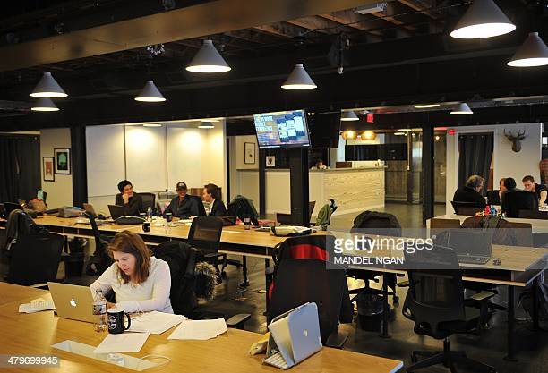 "People work at tables inside of the ""WeWork"" co-operative co-working space on March 13, 2013 in Washington, DC.In a large warehouse-type office in..."