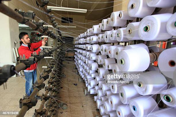 People work at the ElHerbavi textile mill that produce Kufiyyeh in Hebron West Bank on March 26 2015 Kufiyyehs that are mostly linked to Palestinian...