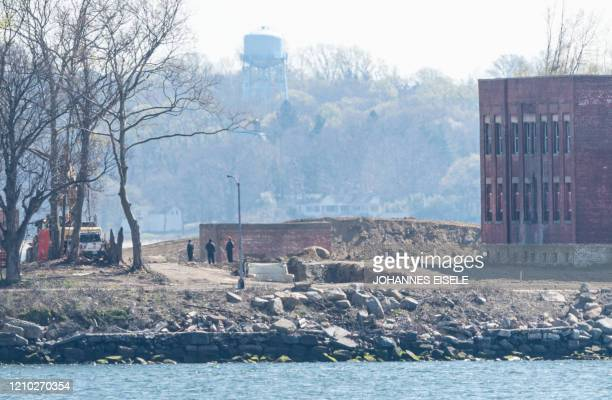 People work next to a trench on Hart Island amid the coronavirus pandemic seen from City Island on April 17 2020 in New York City As New York state...