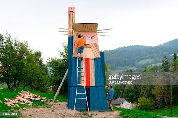 People work on a wooden statue made to resemble US President Donald Trump in the village of Sela pri Kamniku about 20 miles northeast of Ljubljana in...