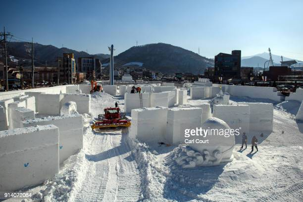 People work on icesculptures on a frozen river ahead of the 2018 Winter Olympics on February 4 2018 in Pyeongchanggun South Korea