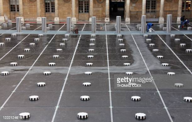 People work on January 5 2010 on the Daniel Buren columns set up in the inner yard of the Palais Royal in central Paris The columns will be...