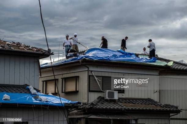 People work to cover a roof that was torn off a house by a tornado shortly before the arrival of Typhoon Hagibis, on October 13, 2019 in Chiba,...