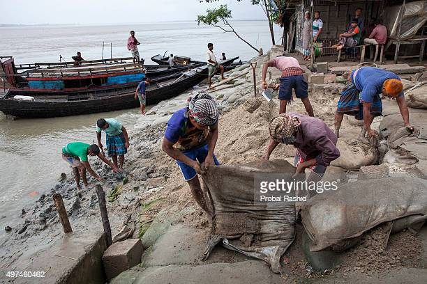 SHYAMNAGAR SATKHIRA KHULNA BANGLADESH People work to repair the embankment designed to protect their island from river erosion Bangladesh is one of...