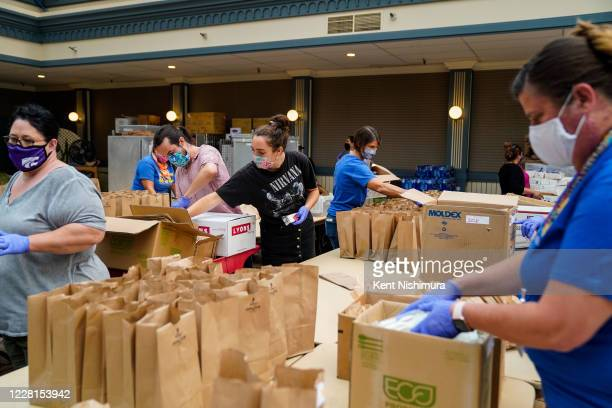 People work together to pack brown bag lunches at an evacuation center at the Boardwalks Coconut Grove at the Santa Cruz Beach Boardwalk during the...