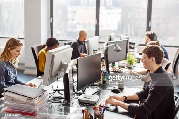 people working at a coworking desk in new office - brasilianischer abstammung stock-fotos und bilder