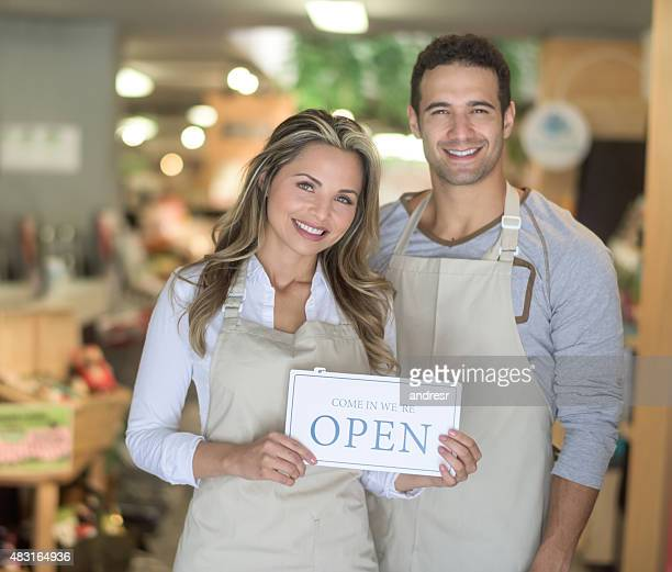 People working at a supermarket and holding an open sign
