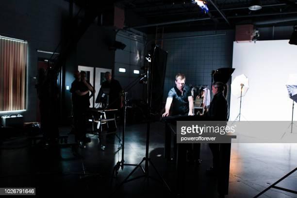 persone che lavorano dietro le quinte durante le riprese di un set cinematografico - set cinematografico foto e immagini stock
