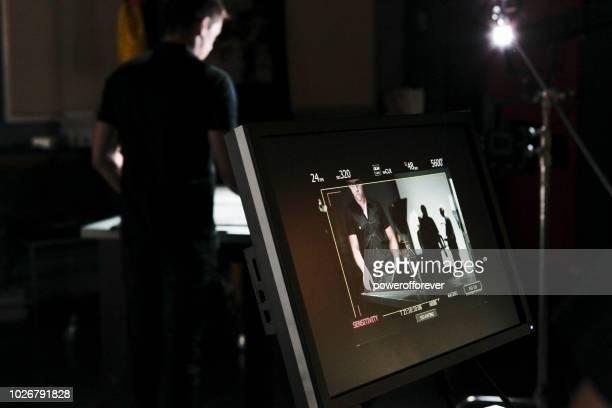 mensen werken achter de schermen tijdens het filmen op een filmset - crew stockfoto's en -beelden
