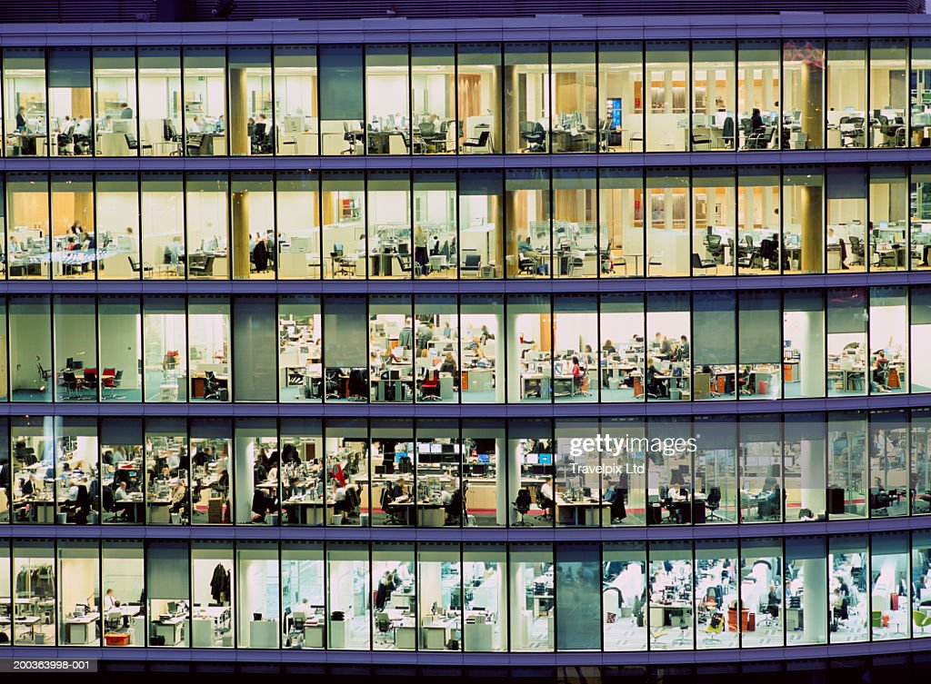 People working in glass sided office building, night : Foto de stock