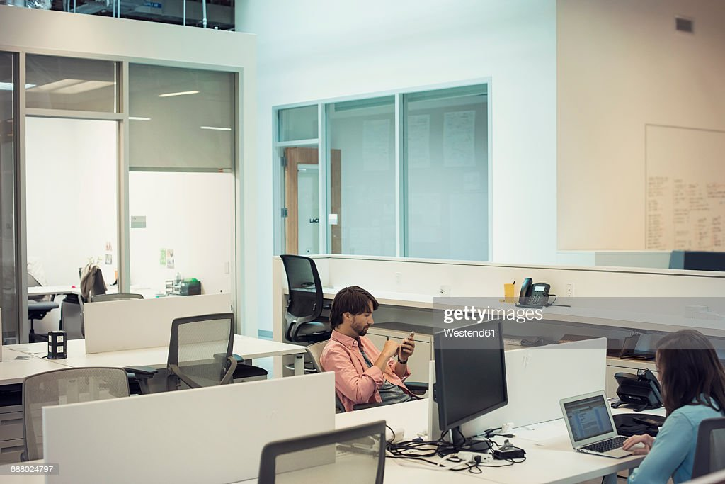 People working in office, using mobile devices : Stock Photo
