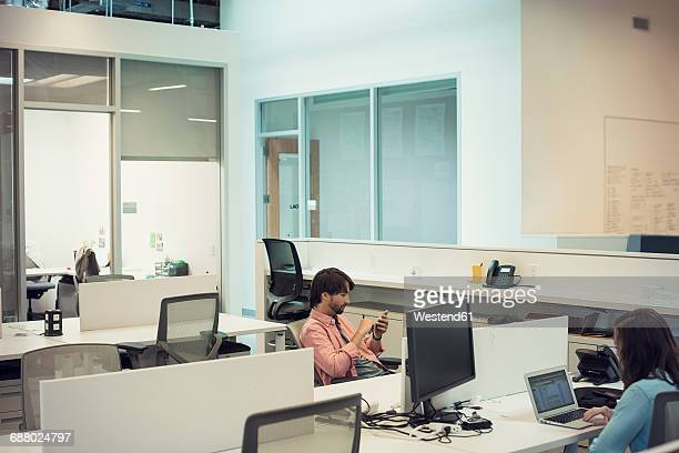People working in office, using mobile devices