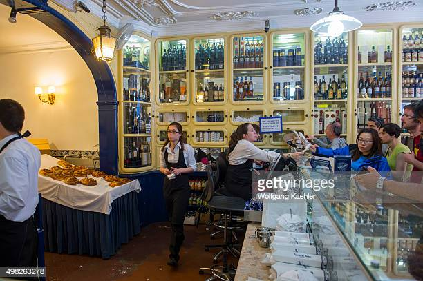 People working in the Pasteis de Belem bakery and store selling Pastel de nata which is a Portuguese egg tart pastry in Lisbon the capital city of...