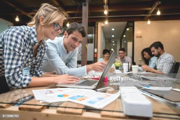 people working online at a creative office - nuova impresa foto e immagini stock