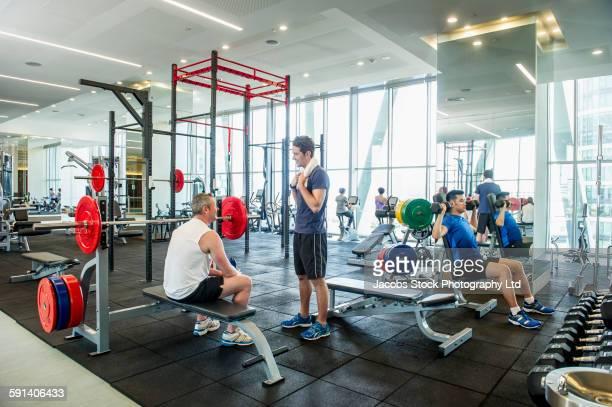 people working out in gymnasium - incidental people fotografías e imágenes de stock