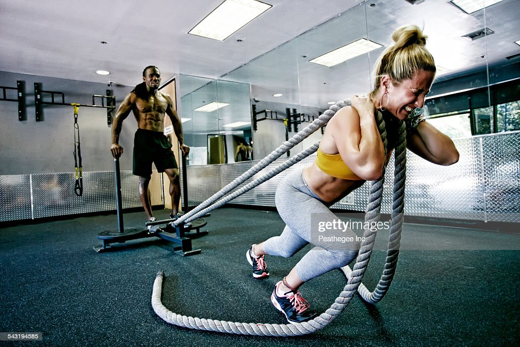 People working out with ropes in gym : Stock Photo