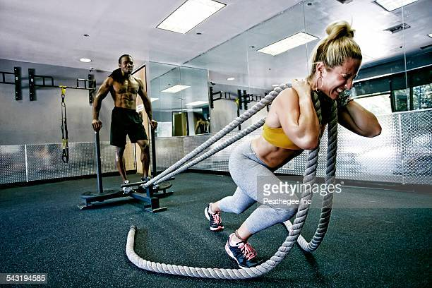 People working out with ropes in gym
