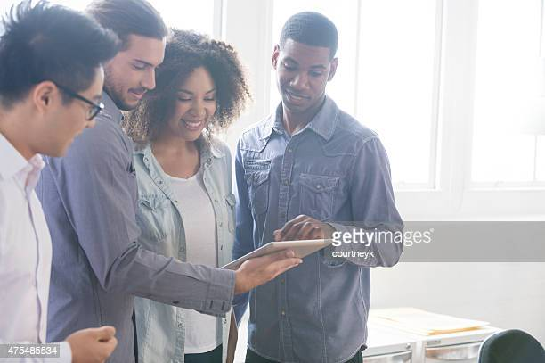 4 people working together on a digital tablet