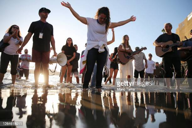 People worship while standing in the Pacific Ocean at the 'Saturate OC' beach revival held amid the COVID-19 pandemic on August 7, 2020 in Newport...