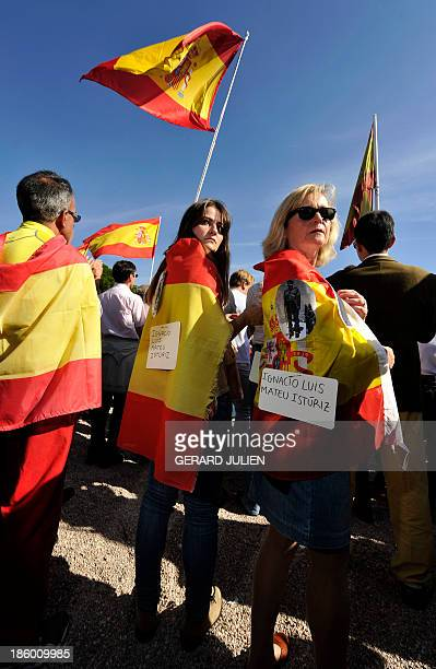 People wrapped in Spanish flags look on as they gather with thousands of Spaniards at Plaza de Colon to answer a call by Association of Victims of...