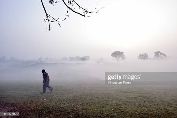 People wrapped in woolen clothes to beat the cold during a foggy morning on January 18 2017 in New Delhi India It recorded the lowest temperature of...