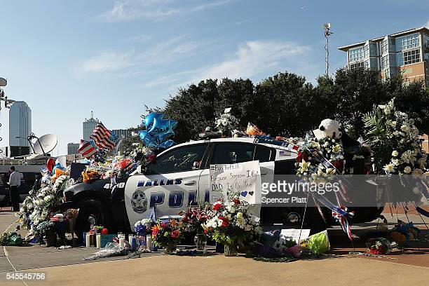 People write condolence notes and lay flowers at a growing memorial in front of the Dallas Police Headquarters near the area that is still an active...