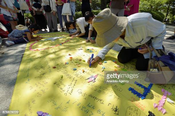 People write down peace messages at Hiroshima Peace Memorial Park on August 6 2017 in Hiroshima Japan Japan marks the 72nd anniversary of the first...