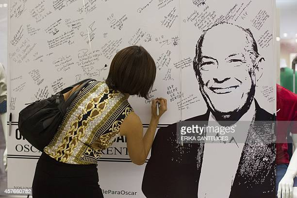 People write messages on a poster with the portrait of late Dominican designer Oscar de la Renta at an Oscar de la Renta store in Santo Domingo on...