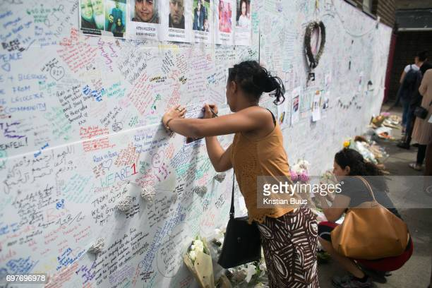 People write messages on a wall for condolences near the tower June 16th 2017 London United Kingdom Grenfell Tower burned out after a catastophic...