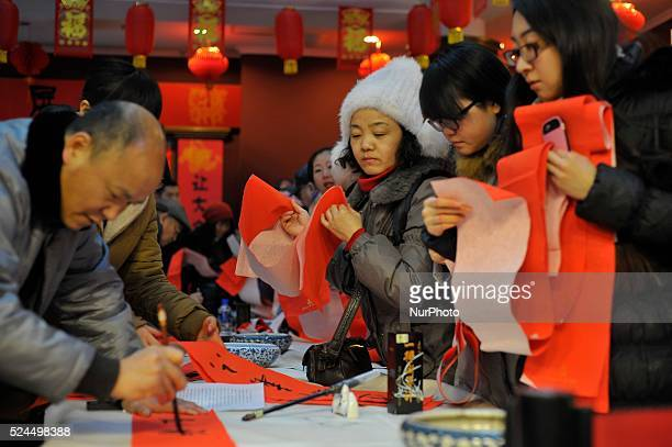 People write the Spring Festival couplets to celebrattion for the upcoming Chinese lunar new year at a Heilongjiang Museum that a festival that falls...