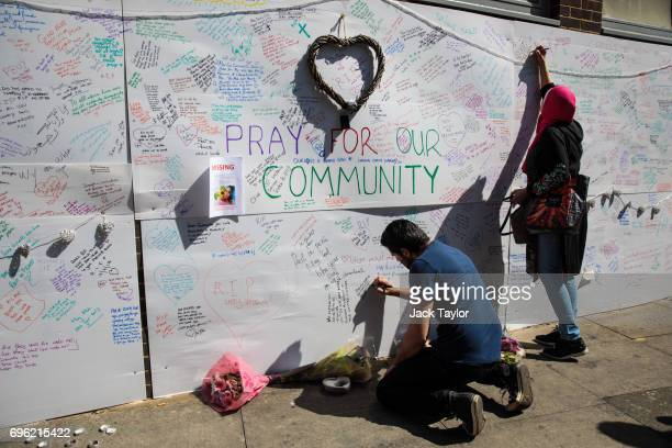 People write tributes and messages of condolence for the victims on a wall near to the site of the Grenfell Tower fire on June 15 2017 in London...