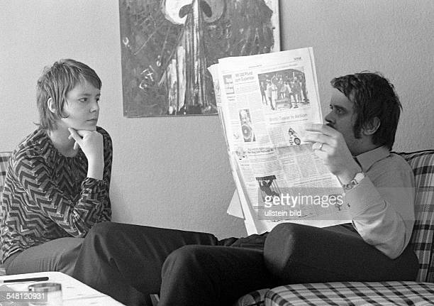 People, young couple sitting in the living room, the man reads a newspaper and ignores the woman, the woman looks very disappointed, aged 20 to 30...