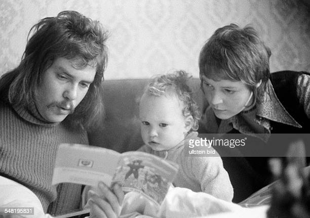 people young family parents read from a picturebook to their child man aged 20 to 28 years woman aged 20 to 25 years girl aged 2 to 3 years Wolfgang...
